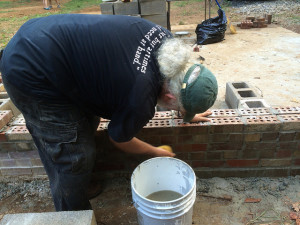 """Bob """"Ever But At Times of Need At Hand"""" washes down the newly laid bricks."""